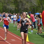 Katelynn Romanchick smiles after crossing the finish line of the 1600 run at the Greater Hartford Invitational on May 14. Romanchick matched the school record of 5:07.69, also earning herself a personal record.